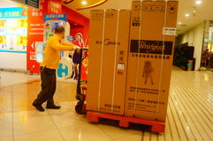 Shenzhen, China: Carrefour supermarket employees carry large appliances into the store Royalty Free Stock Image