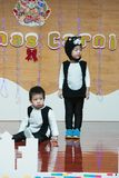 SHENZHEN, CHINA, 2011-12-23: Chinese kids in cat`s costumes perf. Orming at improvised stage at kindergarten Christmas party Stock Photos
