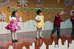 SHENZHEN, CHINA, 2011-12-23: Chinese kids in flower costumes per. Forming at improvised stage at kindergarten Christmas party Royalty Free Stock Image
