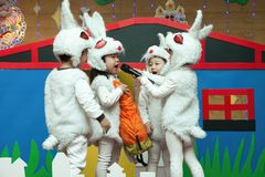 SHENZHEN, CHINA, 2011-12-23: Chinese kids in rabbit`s costumes p. Erforming at improvised stage at kindergarten Christmas party Stock Photography
