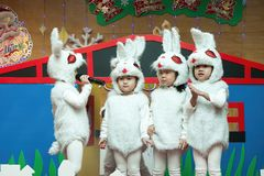 SHENZHEN, CHINA, 2011-12-23: Chinese kids in rabbit`s costumes p. Erforming at improvised stage at kindergarten Christmas party Royalty Free Stock Photo