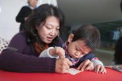 SHENZHEN, CHINA, 2011-12-23: Chinese moeder en haar zoon het vullen Royalty-vrije Stock Foto