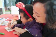 SHENZHEN, CHINA, 2011-12-23: Chinese moeder en haar zoon het vullen Stock Foto
