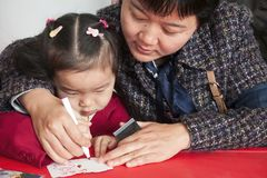 SHENZHEN, CHINA, 2011-12-23: Chinesische Mutter und ihre füllende Postkarte des Sohns an der Weihnachtsfeier in einem Kindergarte Stockbilder