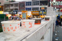 Shenzhen, China: Commercial Street on the fence to be discarded are chowhound paper bowl Royalty Free Stock Images
