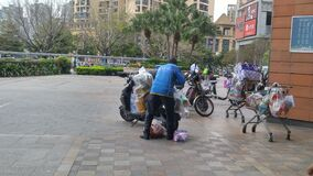 Shenzhen, China: couriers pack and transport items at the entrance to a shopping mall