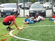 Shenzhen, China: De basisvaardigheden van kinderen in de opleiding van voetbal Stock Afbeeldingen
