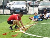 Shenzhen, China: De basisvaardigheden van kinderen in de opleiding van voetbal Stock Fotografie