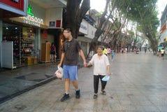 Shenzhen, China: de jonge jongens overhandigen greep oude vrouwengang Stock Afbeelding