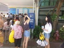 Shenzhen, China: de jongens en de meisjes gaan naar het zwembad kaartjes kopen en gaan zwemmend Stock Afbeelding