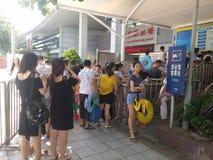 Shenzhen, China: de jongens en de meisjes gaan naar het zwembad kaartjes kopen en gaan zwemmend Stock Fotografie