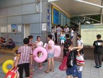 Shenzhen, China: de jongens en de meisjes gaan naar het zwembad kaartjes kopen en gaan zwemmend Royalty-vrije Stock Afbeeldingen