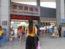 Shenzhen, China: de jongens en de meisjes gaan naar het zwembad kaartjes kopen en gaan zwemmend Stock Afbeeldingen