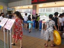 Shenzhen, China: de jongens en de meisjes gaan naar het zwembad kaartjes kopen en gaan zwemmend Stock Foto's