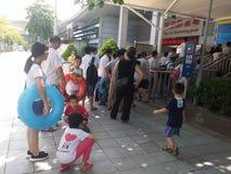 Shenzhen, China: de jongens en de meisjes gaan naar het zwembad kaartjes kopen en gaan zwemmend Stock Foto