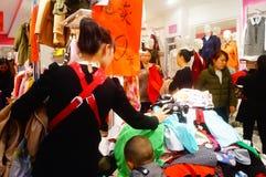 Shenzhen, China: de kledende opslag voorzien kleding, vrouwen koopt Royalty-vrije Stock Afbeeldingen