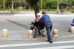 Shenzhen, China: de mensen duwden de rolstoel Stock Afbeeldingen