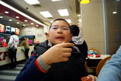 Shenzhen, china: eat in kfc restaurant. Shenzhen Baoan Xixiang pedestrian street, the KFC restaurant, a boy eating delicious food Royalty Free Stock Photos