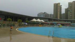 Shenzhen, China: Es das ` s, das sonnig ist, es das regnerische ` s, Männer und Frauen im Swimmingpool entweder schwimmen oder ne stock video