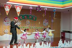 SHENZHEN, CHINA, 2011-12-23: European kindergarten teacher perfo. Rming with Chinese kids at Christmas party Stock Photos