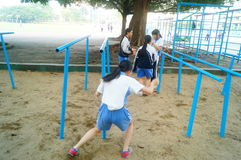 Shenzhen, China: female middle school students in the horizontal bar exercise Royalty Free Stock Photo