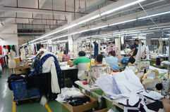 Shenzhen, China: garment factory workshop. Shenzhen Longhua District, Dalang street, garment factory workshop, the workers are making clothing stock photo