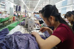 Shenzhen, China: garment factory workshop. Shenzhen Longhua District, Dalang street, garment factory workshop, the workers are making clothing royalty free stock image