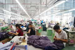Shenzhen, China: garment factory workshop. Shenzhen Longhua District, Dalang street, garment factory workshop, the workers are making clothing Stock Photos