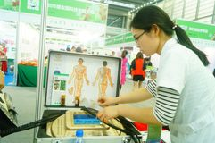Shenzhen, China: health care exhibition, electronic acupuncture experience. A woman is experiencing the efficacy of electronic acupuncture apparatus at the royalty free stock image