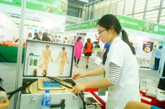 Shenzhen, China: health care exhibition, electronic acupuncture experience. A woman is experiencing the efficacy of electronic acupuncture apparatus at the stock images