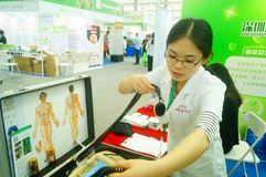 Shenzhen, China: health care exhibition, electronic acupuncture experience. A woman is experiencing the efficacy of electronic acupuncture apparatus at the royalty free stock photography