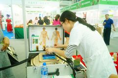 Shenzhen, China: health care exhibition, electronic acupuncture experience. A woman is experiencing the efficacy of electronic acupuncture apparatus at the stock image