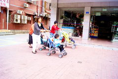 Shenzhen China: jonge moeder drie die buggies duwt Stock Foto