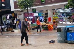 Shenzhen, China: a man with a mental illness picks up food from a dustbin Royalty Free Stock Image