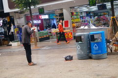 Shenzhen, China: a man with a mental illness picks up food from a dustbin Stock Photos
