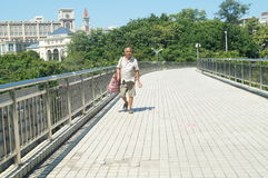 Shenzhen, China: pedestrian bridge, a man picking up waste Stock Photo