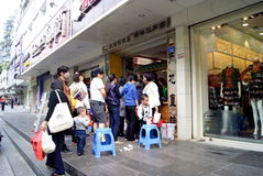 Shenzhen china: people are waiting in line in the front of the shop Stock Photo