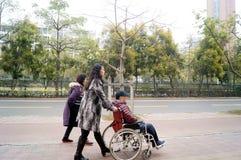 Shenzhen, China: pushing a wheelchair bound elderly Royalty Free Stock Photography