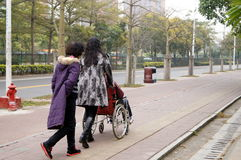 Shenzhen, China: pushing a wheelchair bound elderly Royalty Free Stock Photos