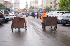 Shenzhen, China: sanitation workers hauling garbage truck Royalty Free Stock Photography