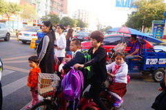 Shenzhen, China: after school, parents take their children home electric bicycle Stock Photos