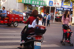 Shenzhen, China: after school, parents take their children home electric bicycle Stock Photo