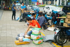 Shenzhen, China: on the sidewalk courier company employees are distributing customer courier Stock Image