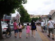 Shenzhen, China: sidewalk, the family walked by Stock Photos