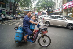 Shenzhen, China: single electric vehicle gas bottle and the little boy Royalty Free Stock Photos