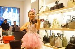 Shenzhen, China: store promotions, the woman playing the violin. Xixiang Shenzhen Tianhong shopping malls, store promotions, a young woman playing the violin to Royalty Free Stock Photo