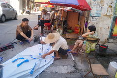Shenzhen, China: street repair old umbrella Stock Photography