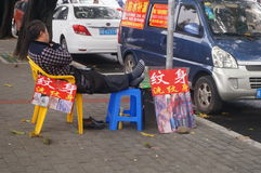 Shenzhen, China: Street tattoo advertising and hawkers. Shenzhen Xixiang, tattoo advertising and street hawkers royalty free stock photo