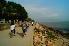 Shenzhen, China: tourists travel by bike in Shenzhen Bay Park Stock Images