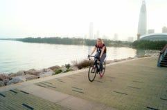 Shenzhen, China: tourists travel by bike in Shenzhen Bay Park Stock Image